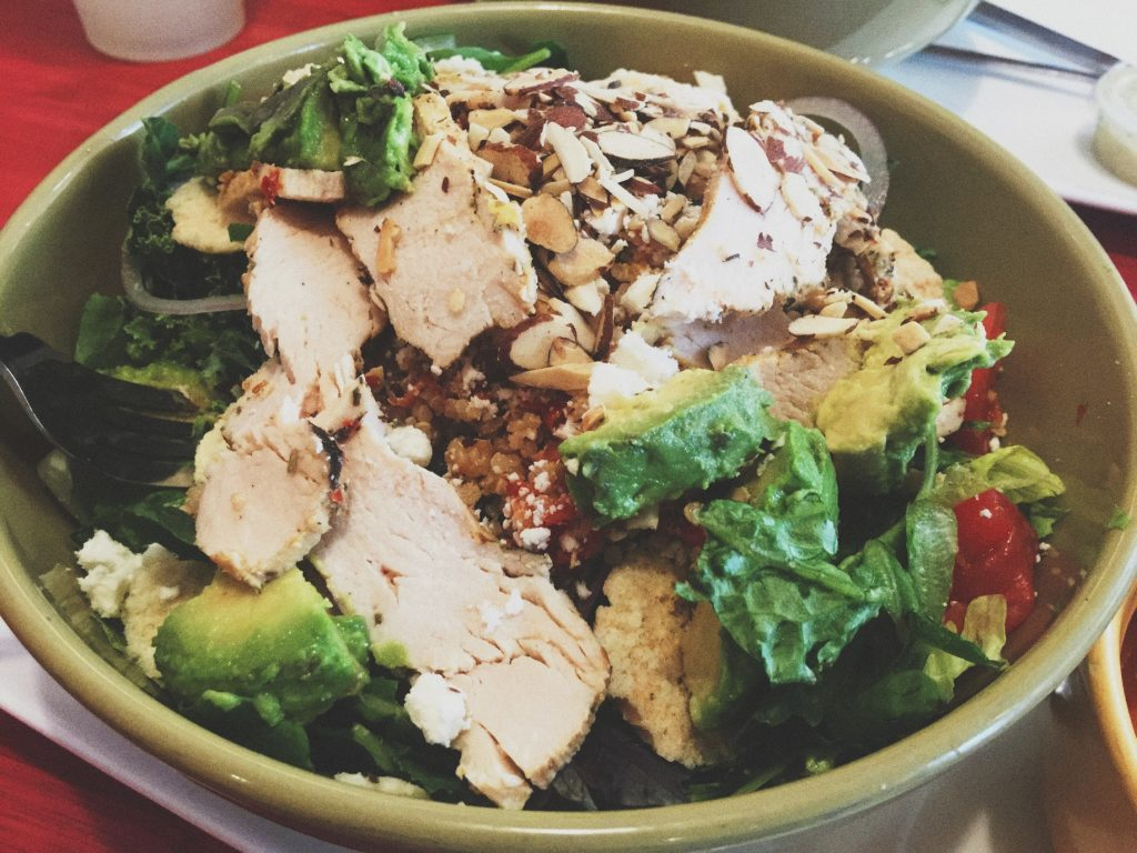 panera bread greek salad with quinoa, chicken, parmesan, almonds, onions, tomato, cucumber, avocado, and greek dressing